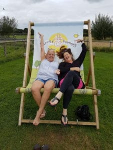 Two adults sitting on the giant deckchair at Farmer Palmer's