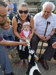Family with baby bottle feeding goat kid at Farmer Palmer's
