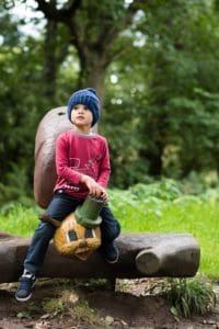 Little boy in bobble hat sat on wooden snail sculpture at Farmer Palmer's