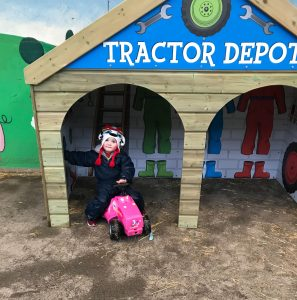 Child sitting on tractor in wooden depot