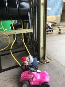 Child pretending to refuel a pedal tractor