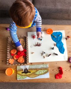 Child playing with farm toys and play dough